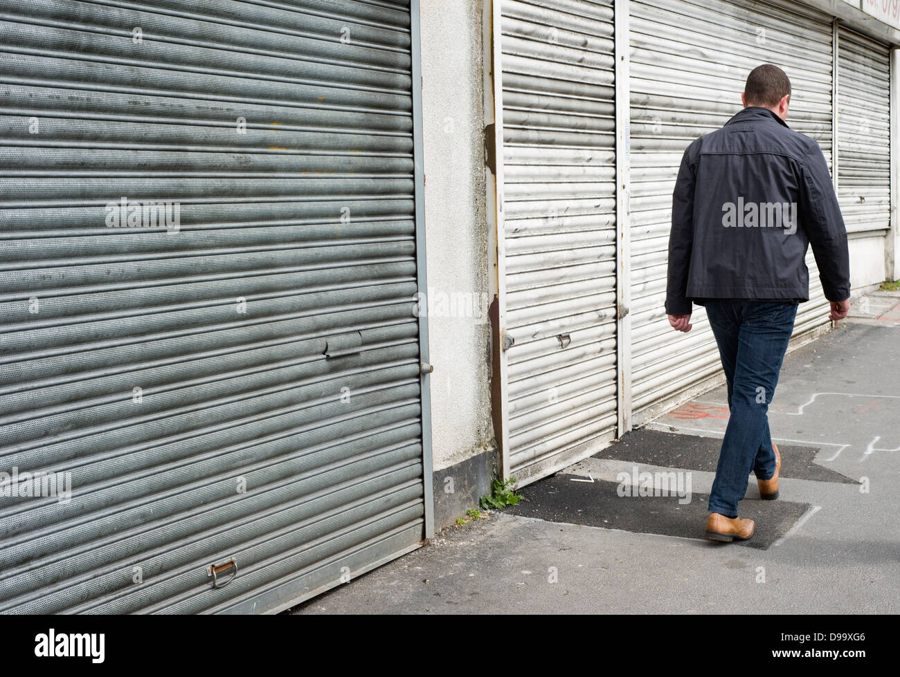 A man walking past a row of closed down shops in Stretford, Manchester, England, UK Stock Photo