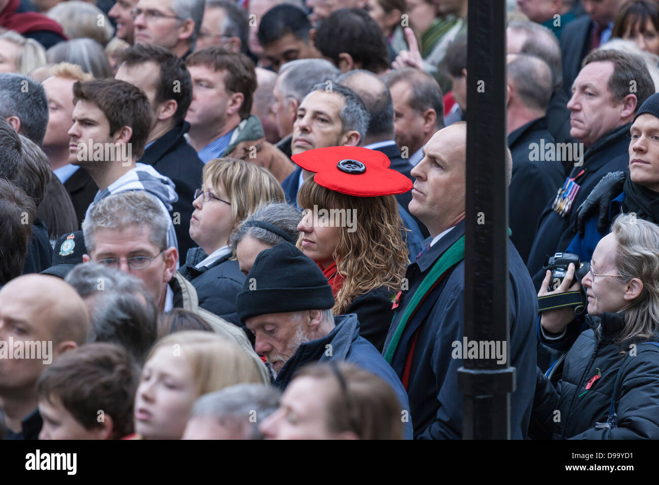 Crowd at the Cenotaph in Whitehall, London on Remembrance Sunday with a woman wearing a distinctive red poppy hat - Stock Image