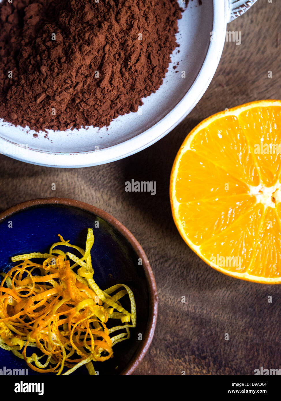 cocoa powder, lemon and orange zest strips, and a half orange showing delicious combination of flavours - Stock Image