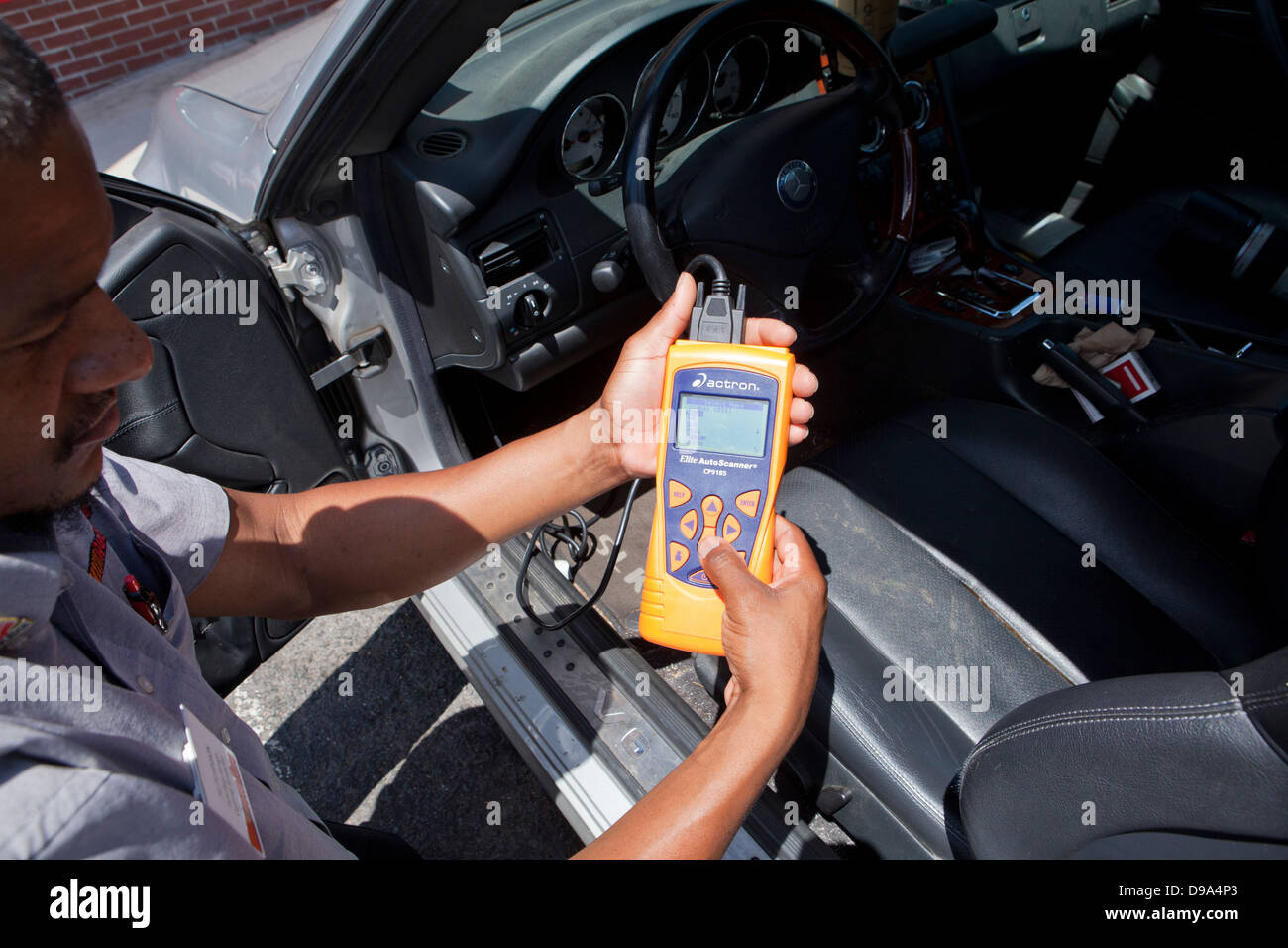 Auto mechanic using car diagnostic scanner (OBD II scanner