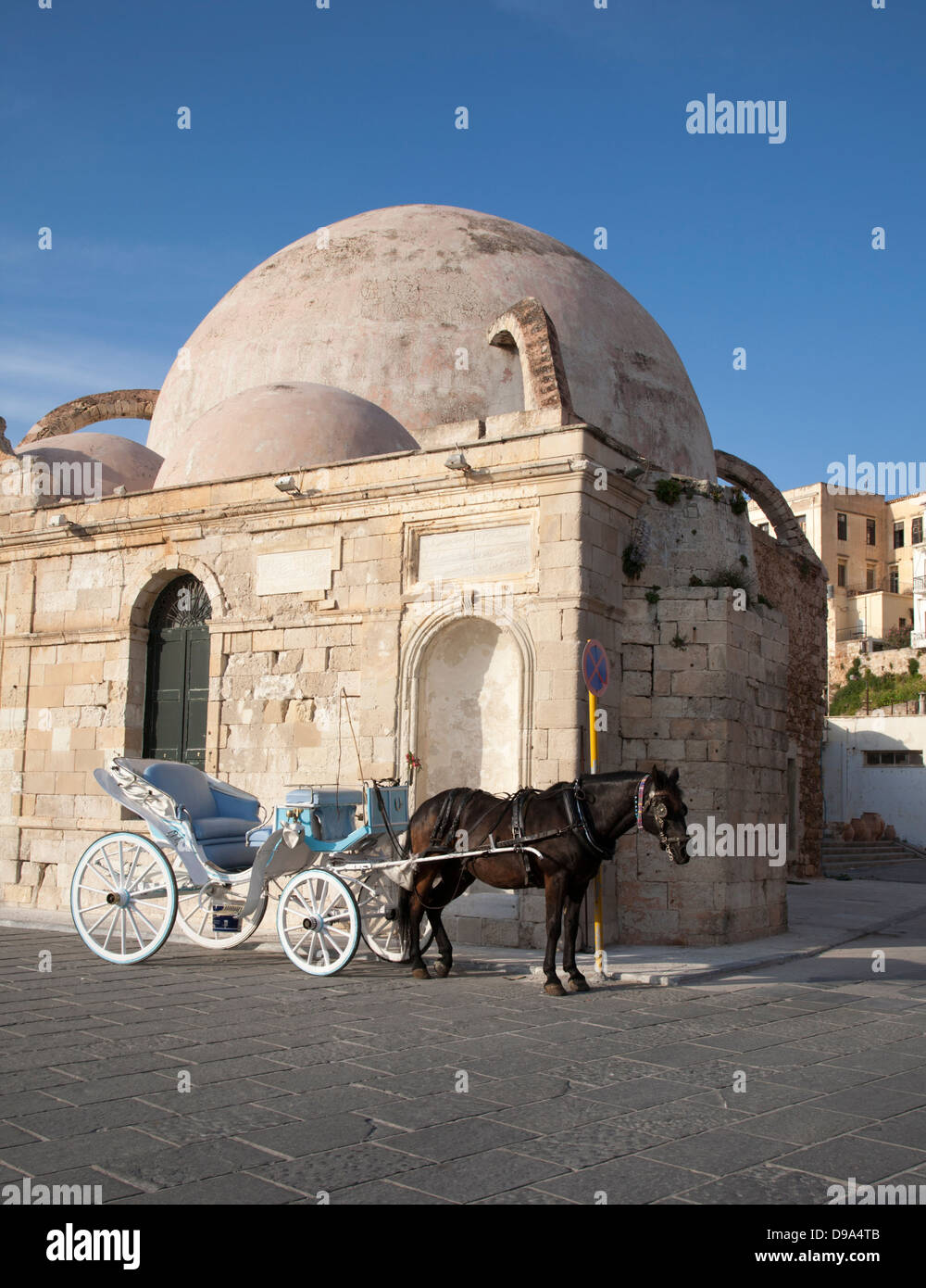 Horse drawn buggy beside the Turkish Yiali Tzami (aka Giali Tzamisi) Mosque at Venetian Harbour in old town Chania - Stock Image