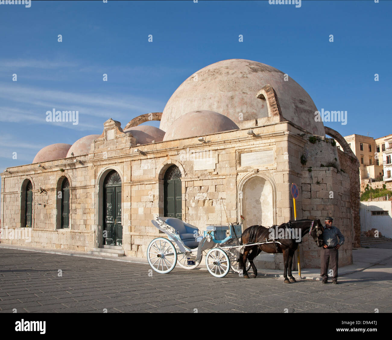 Horse with carriage and driver beside the Turkish Yiali Tzami  Mosque at Venetian Harbour in old town Chania - Stock Image