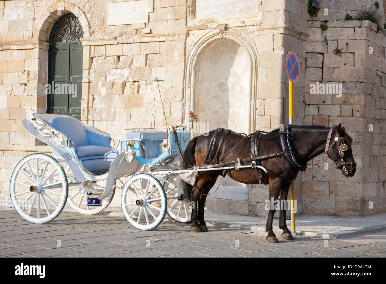 Horse drawn taxi beside the Turkish Yiali Tzami (aka Giali Tzamisi) Mosque at Venetian Harbour in old town Chania - Stock Image