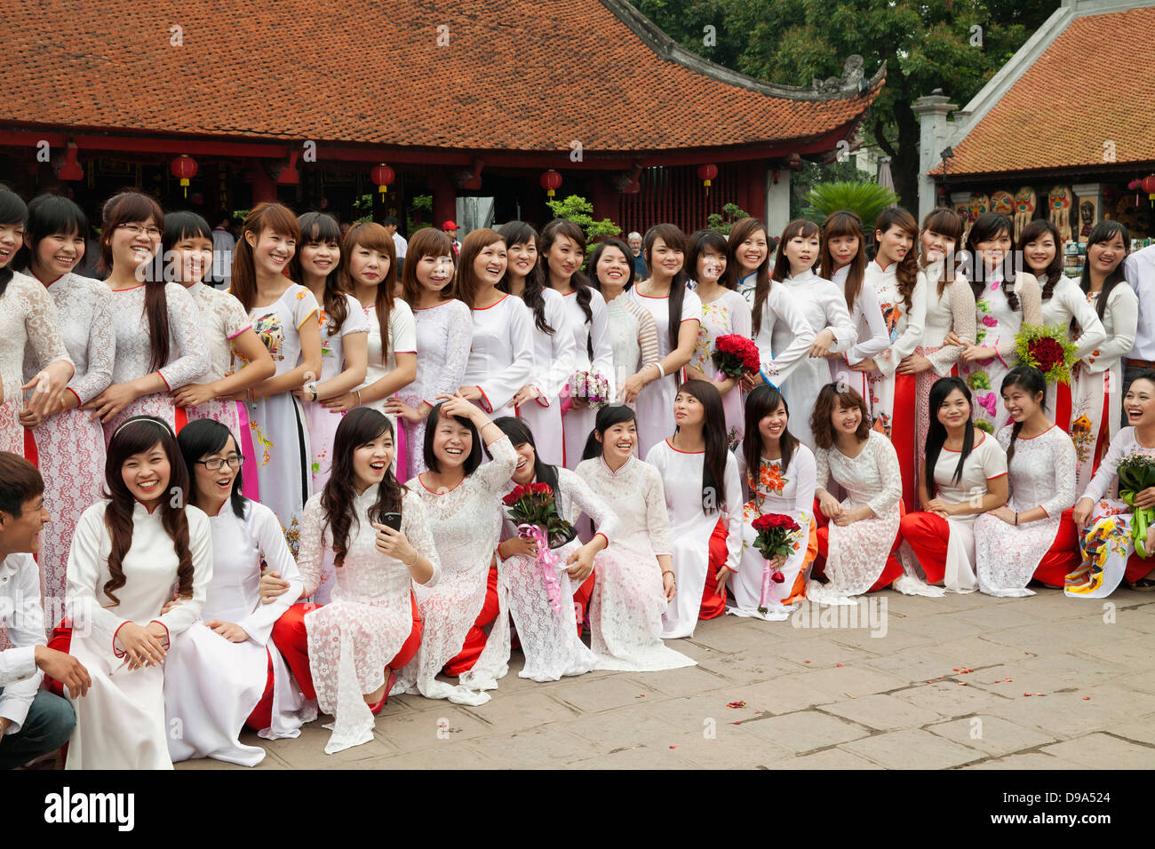 Young female college graduates pose for a portrait at the Temple of Literature in Hanoi, Vietnam, Southeast Asia Stock Photo