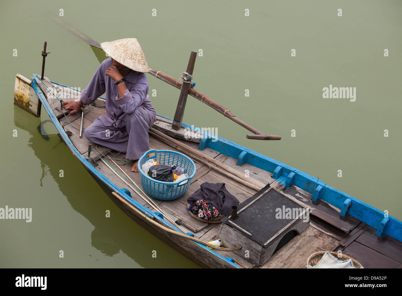 Man in boat on river near Hoi An, Vietnam - Stock Image