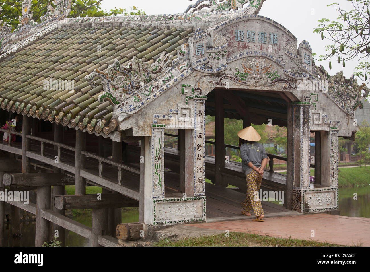 Woman in conical hat crossing Thanh Toan footbridge in Thuy Thanh village outside of Hue, Thừa Thiên–Huế province, - Stock Image
