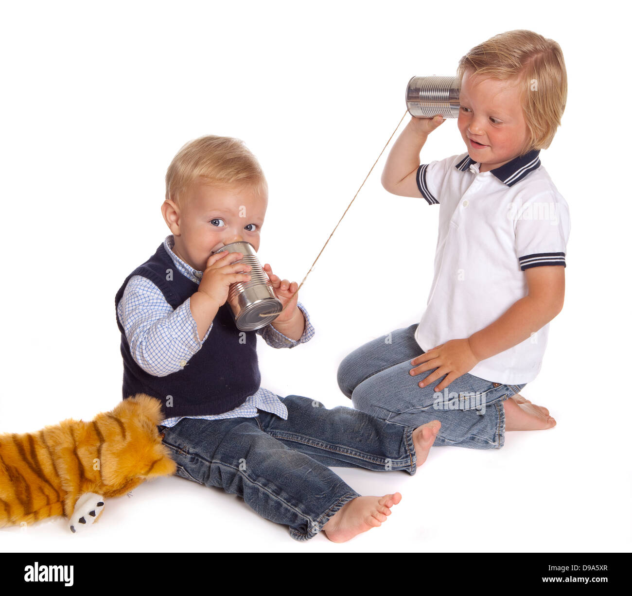Two little brothers talking on the phone using two cans and a piece of rope - Stock Image