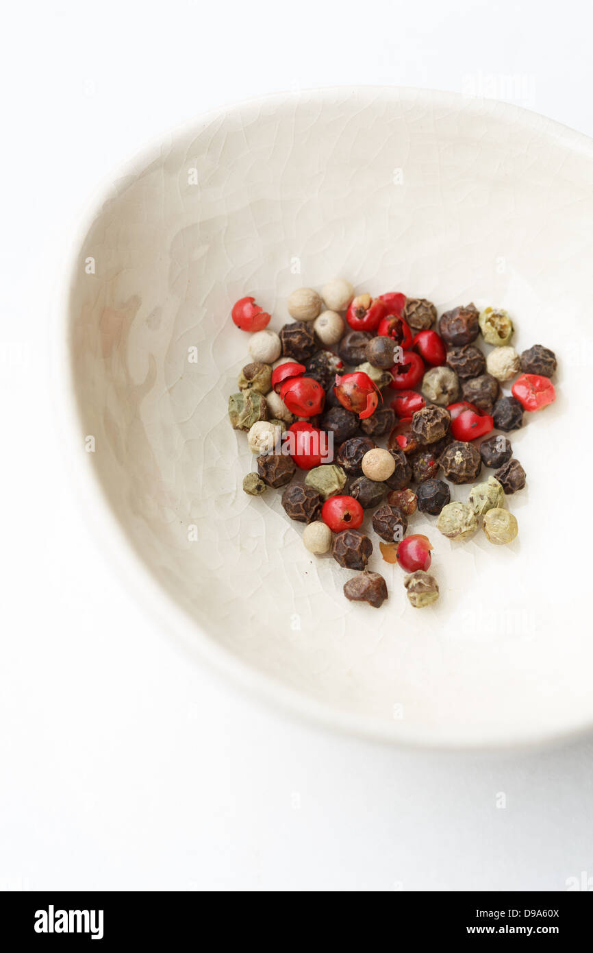 White bowl with variety of peppercorns - Stock Image