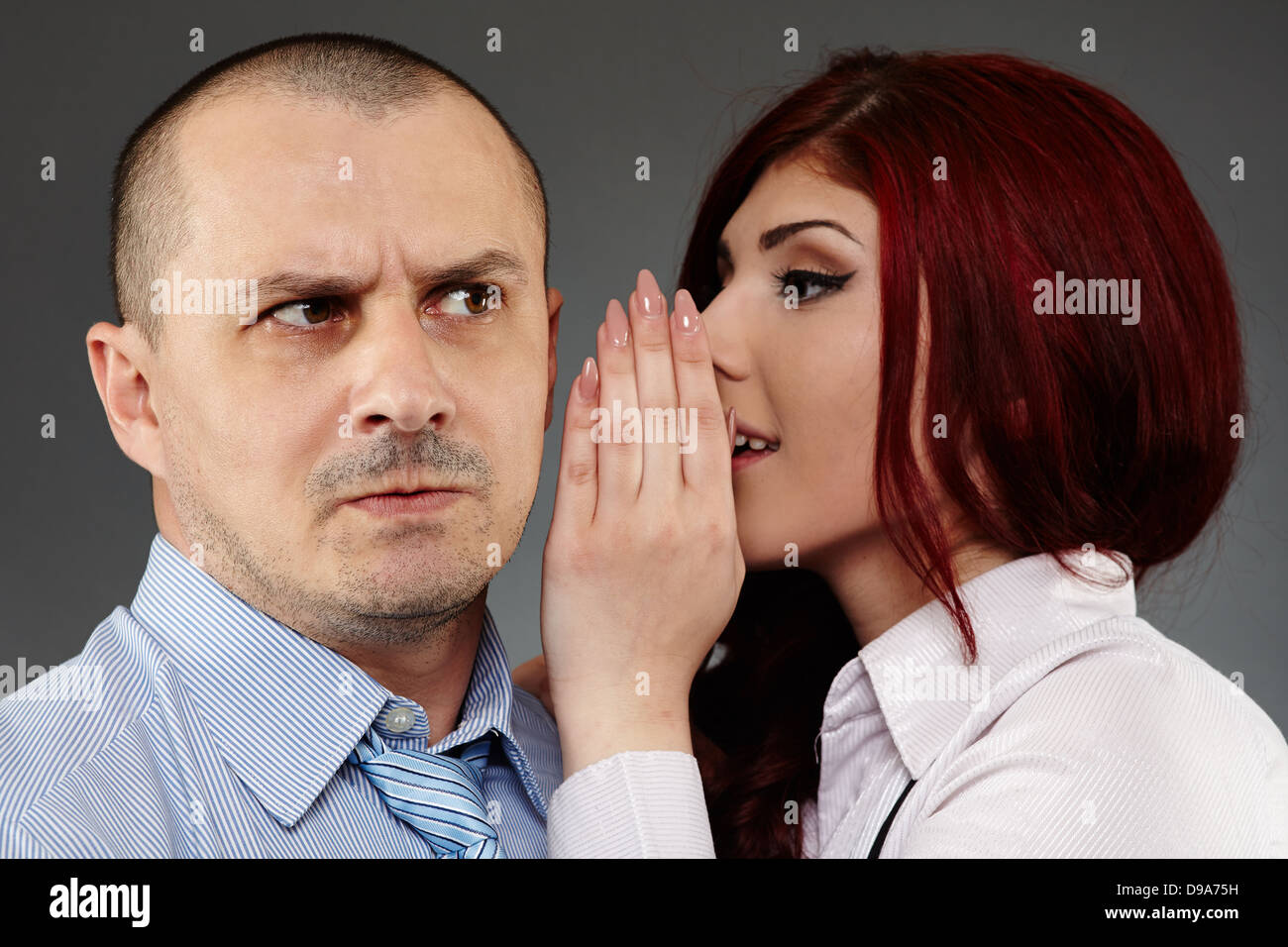 Secretary sharing some secrets to her boss, studio shot - Stock Image