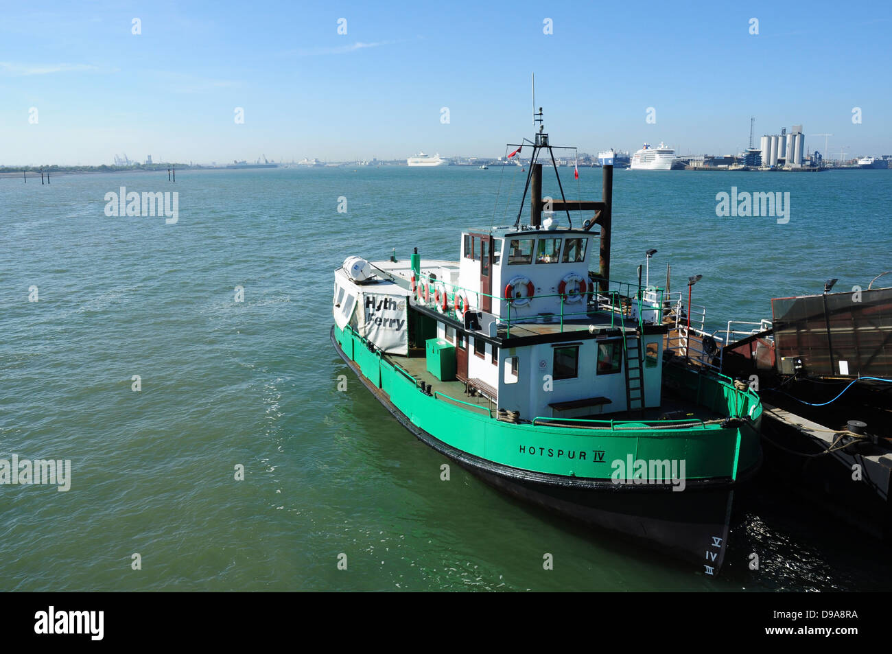 Hythe Ferry for Southampton at Hythe pier head with Southampton docks and ships in background, Hampshire, England, - Stock Image