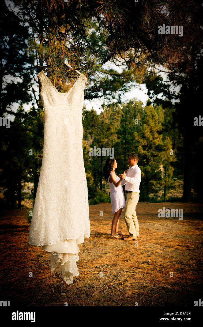 Couple dance in forest with wedding dress hanging from tree Stock ...