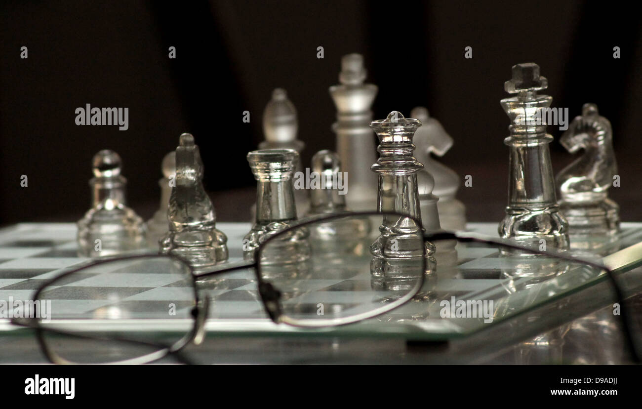 a transparent chess set board with a pair of glasses - Stock Image
