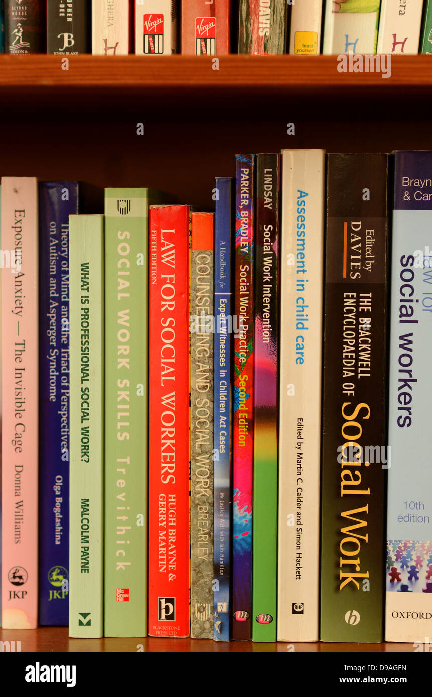 Social Work reference books on a bookshelf - Stock Image