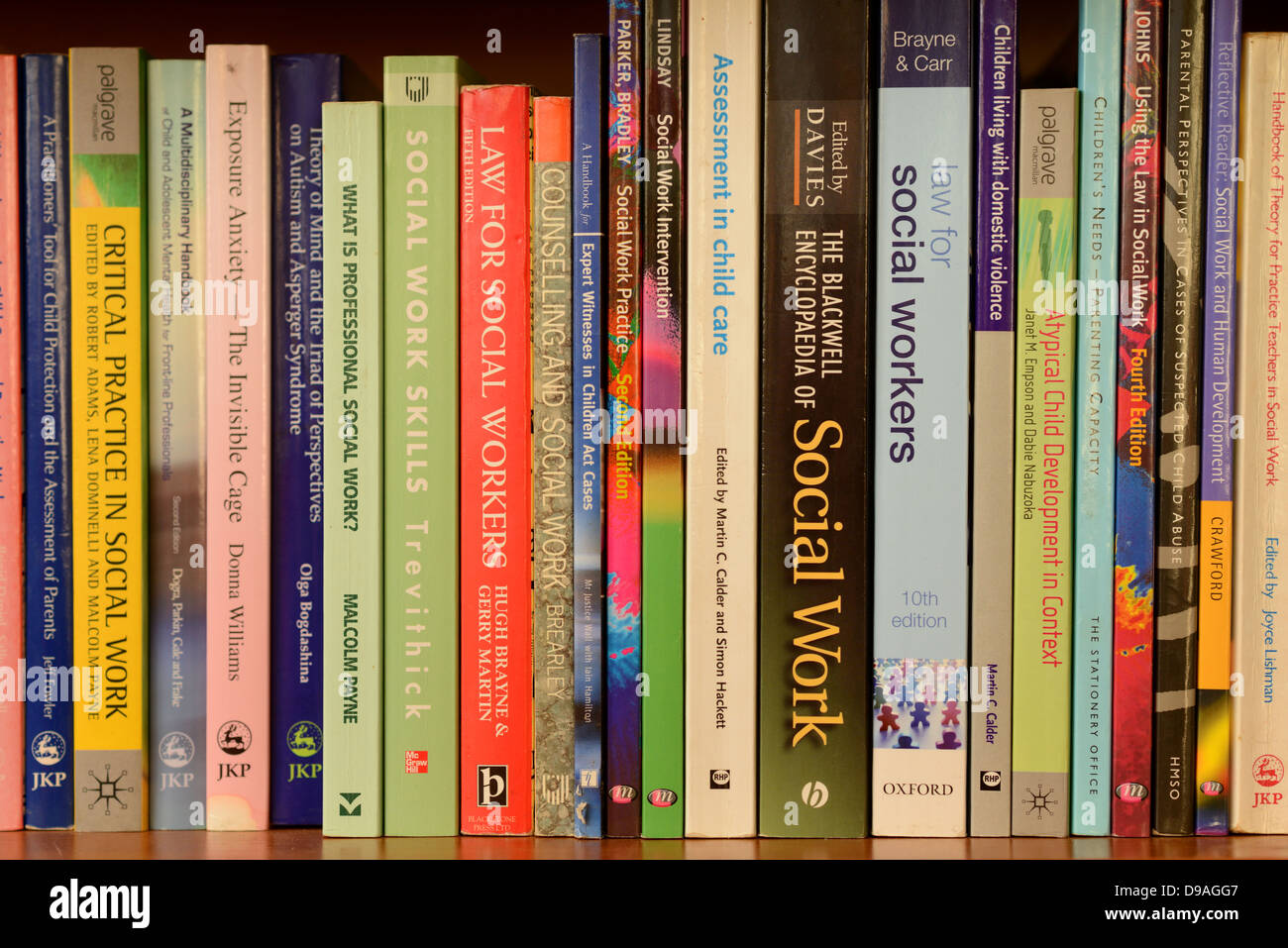 Social Work text books on a bookshelf - Stock Image