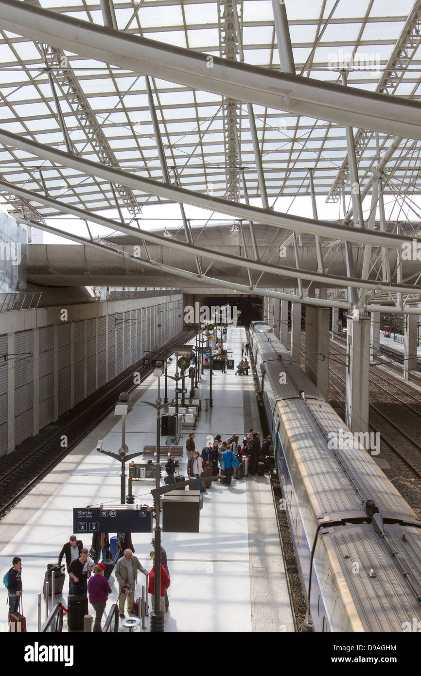 Travelers boarding a train from the platform at Chalres de Gaulle Train Station in Paris France - Stock Image
