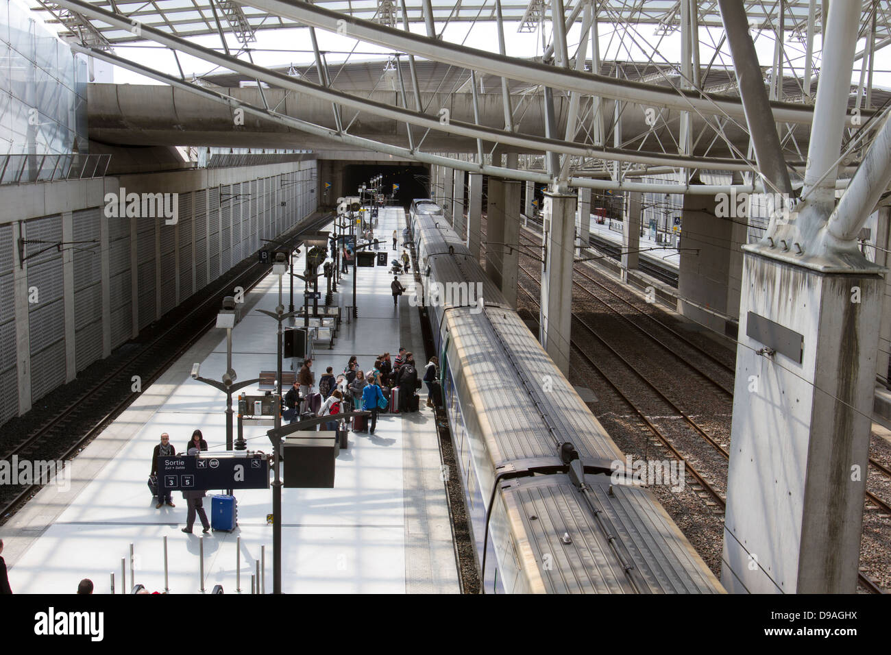 Travelers boarding a train from the platform at Charles de Gaulle Train Station in Paris France - Stock Image