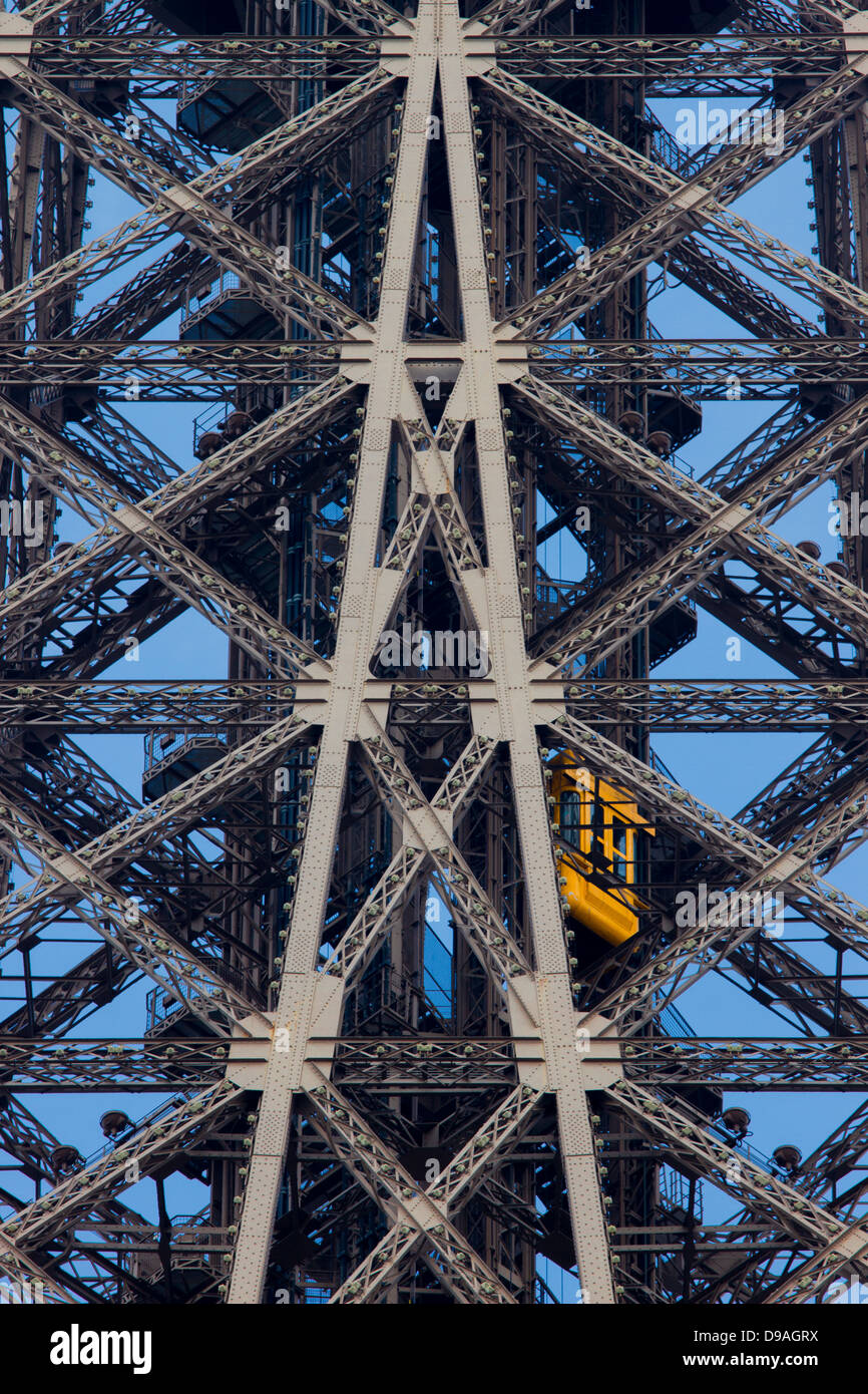 Bright orange elevator climbing through complex lattice ironwork to the top of the Eiffel Tower - Stock Image