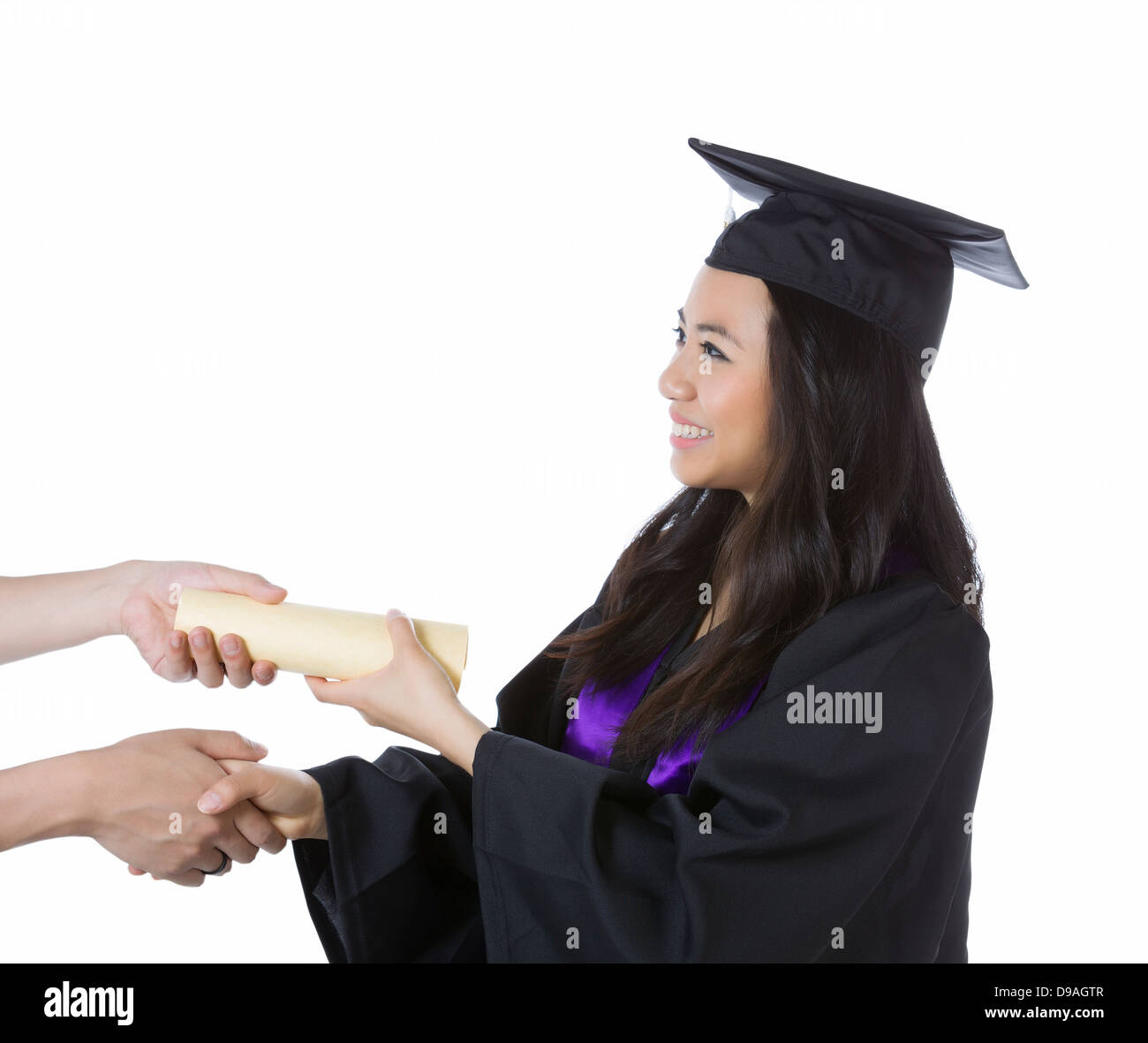 Young adult woman graduating from college while getting her diploma on pure white background - Stock Image