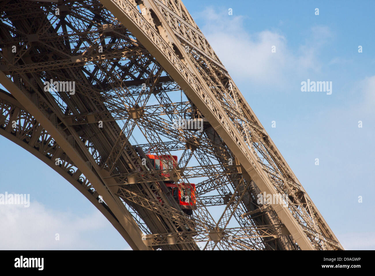 Two bright red elevators climbing up one of Eiffel Tower iron girders bringing tourists to the first floor Stock Photo