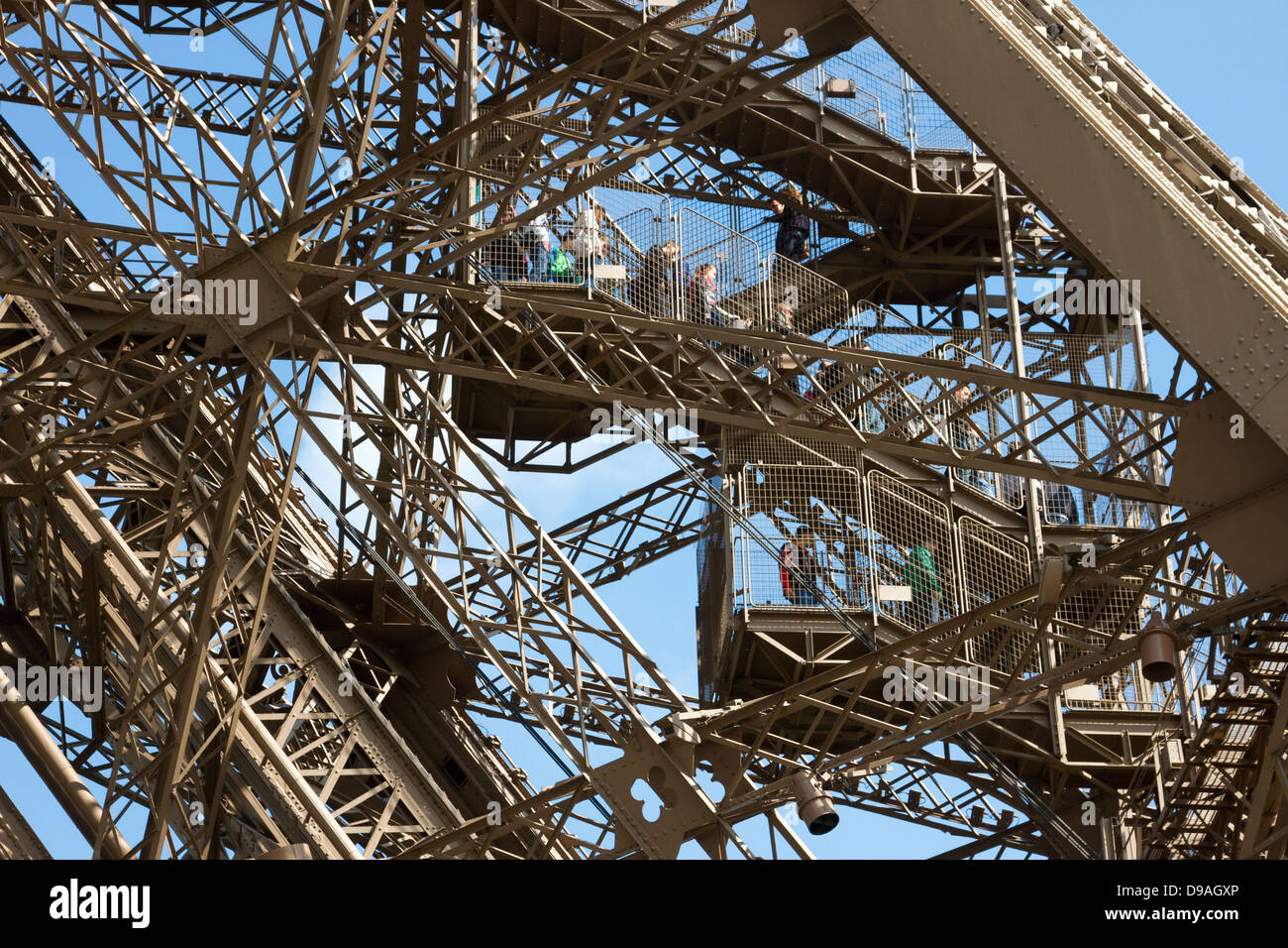 Tourists walking down steps through complex lattice iron girders to descend from first level of Eiffel Tower in Stock Photo