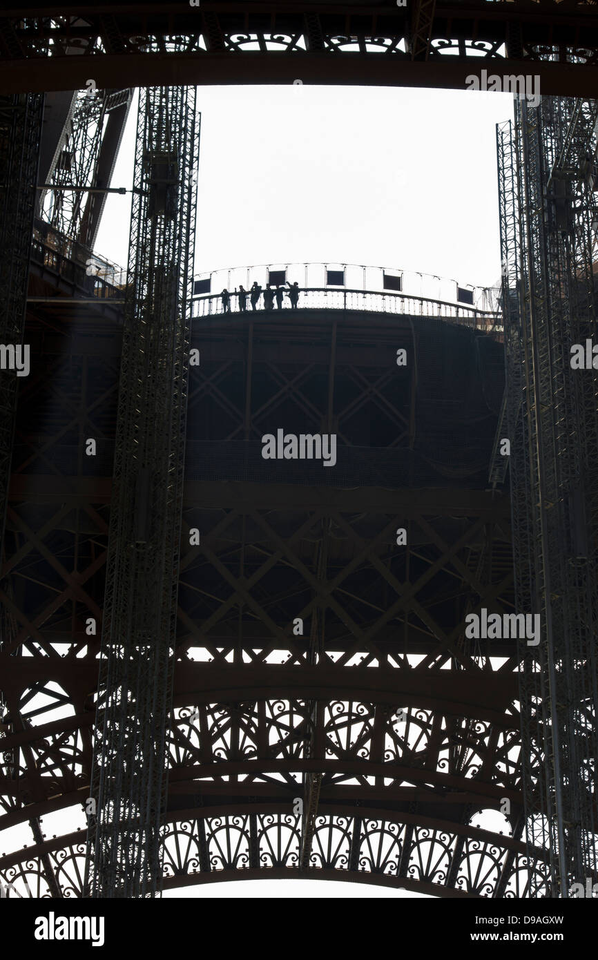 Silhouette of people looking out from first level platform of Eiffel Tower surrounded by decorative ironwork - Stock Image