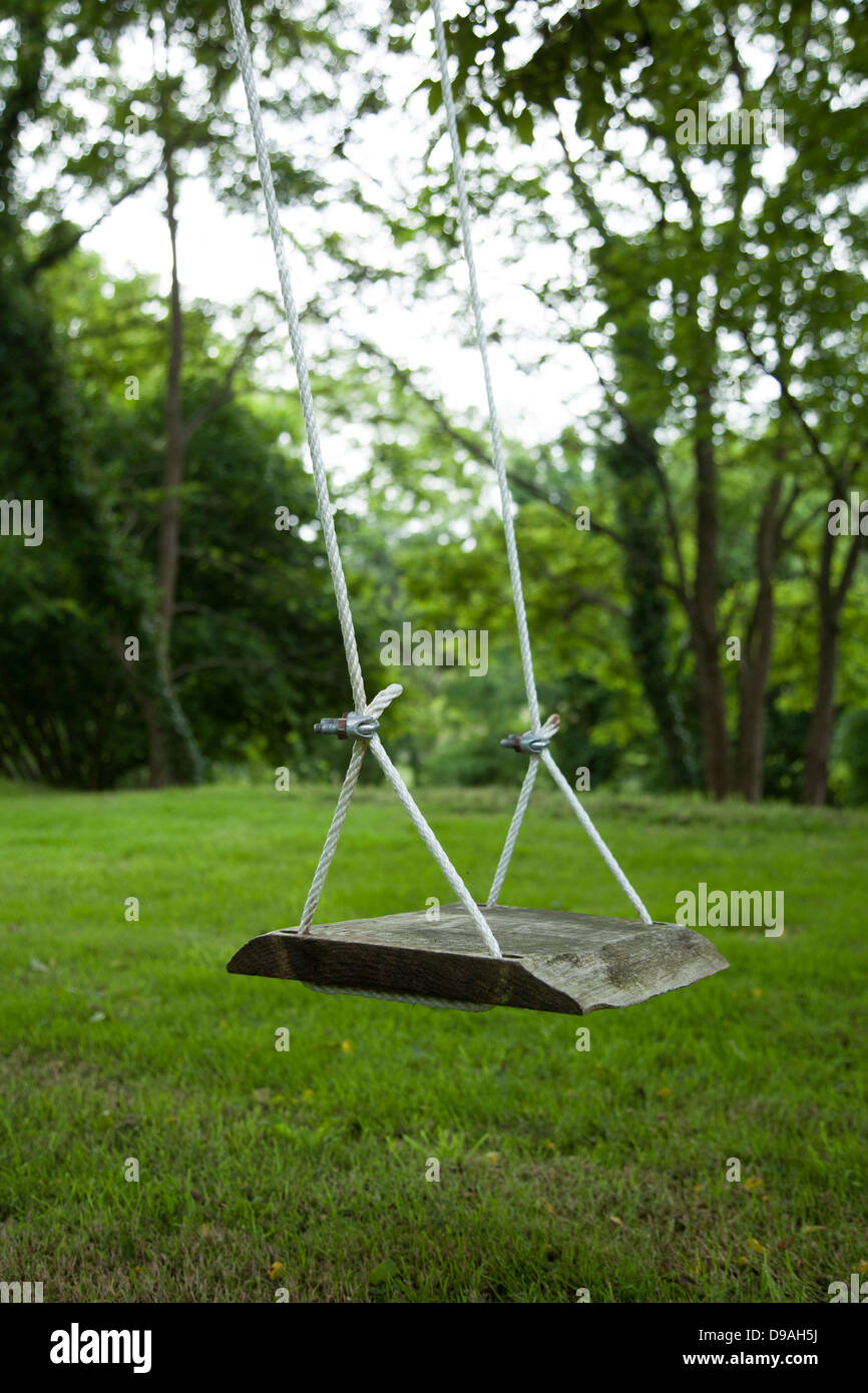 An empty wooden swing in a picturesque garden. - Stock Image