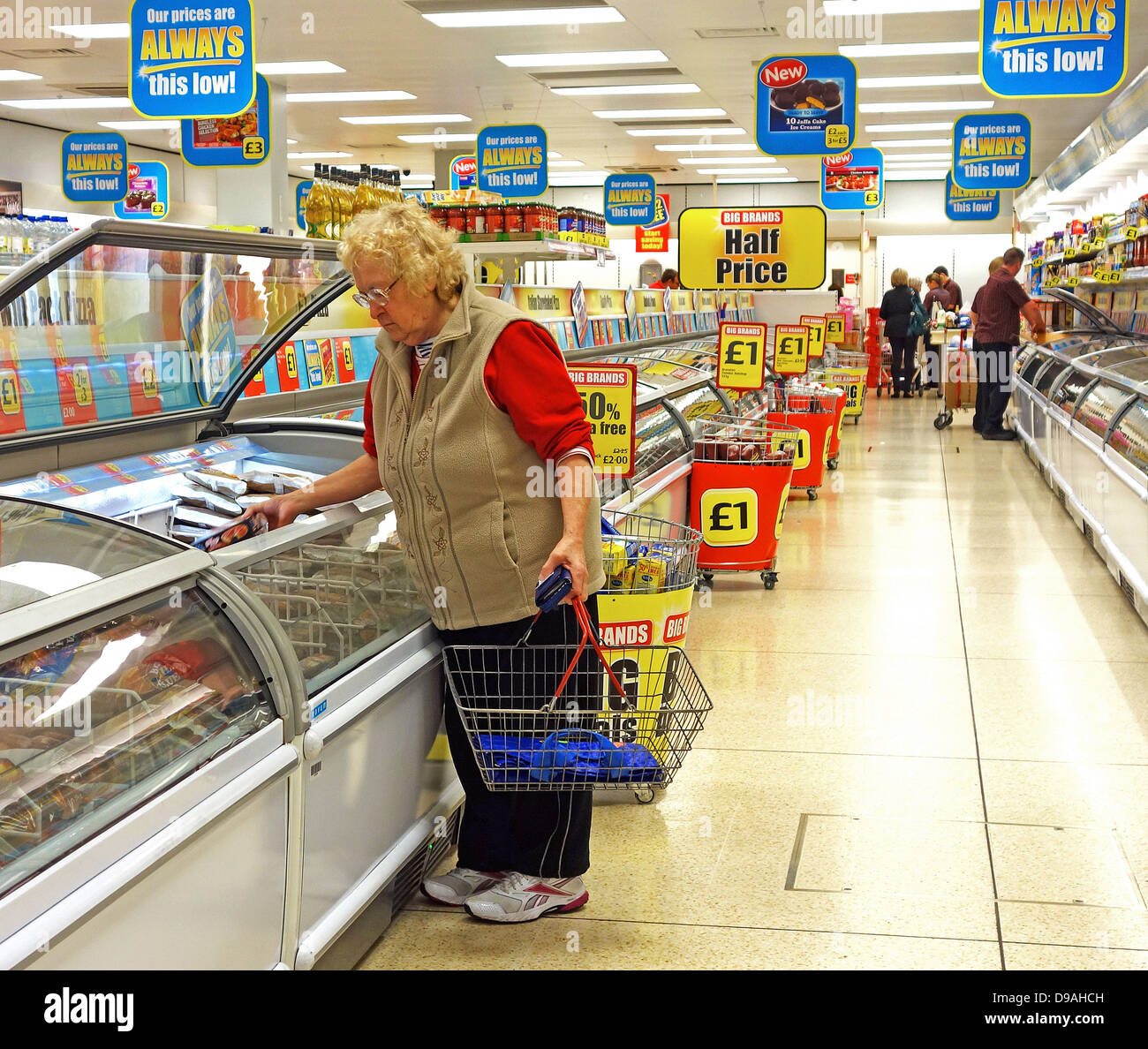 An elderly woman shopping in an iceland store, uk - Stock Image