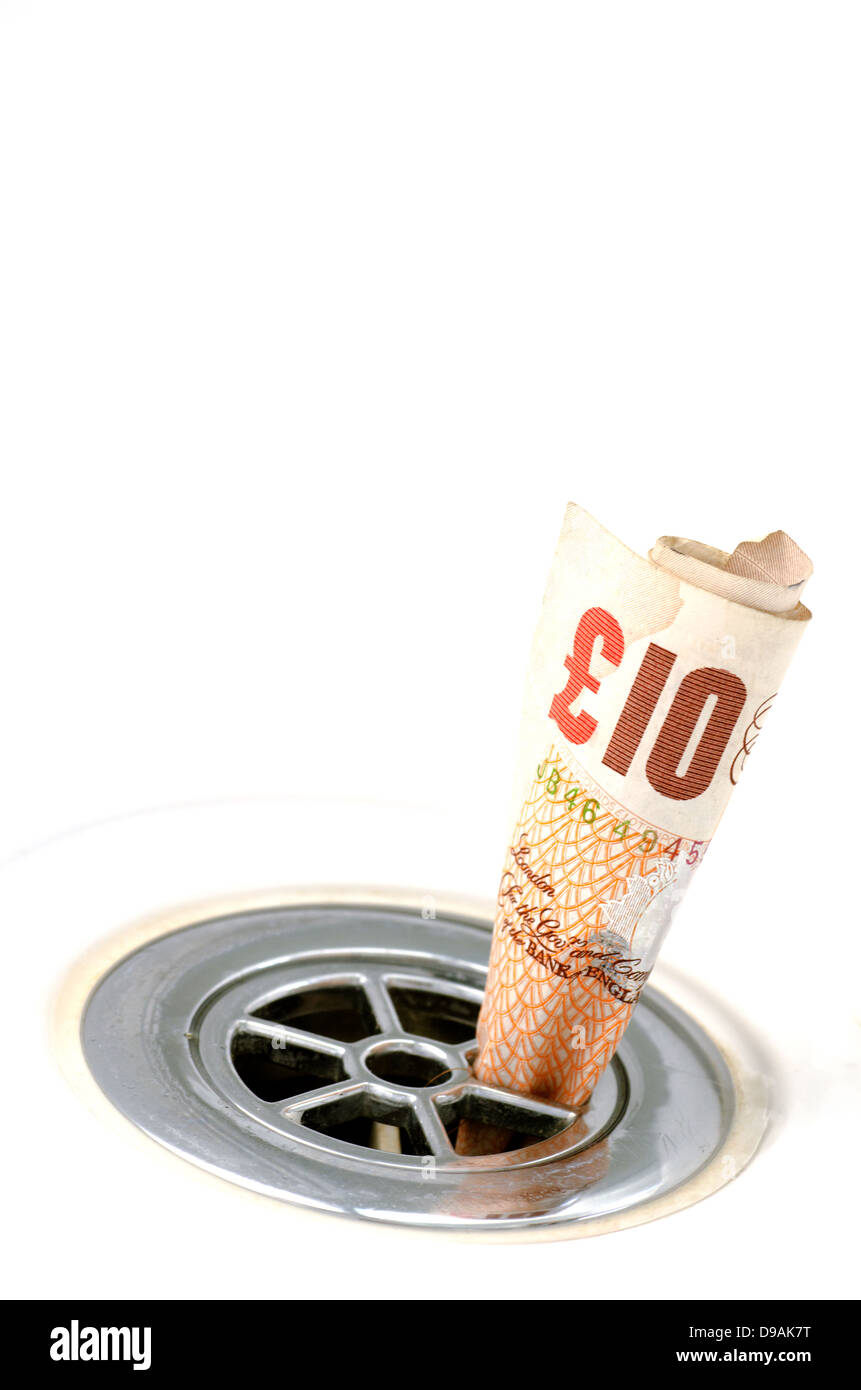 Rolled up ten pound note in a plug hole - Stock Image