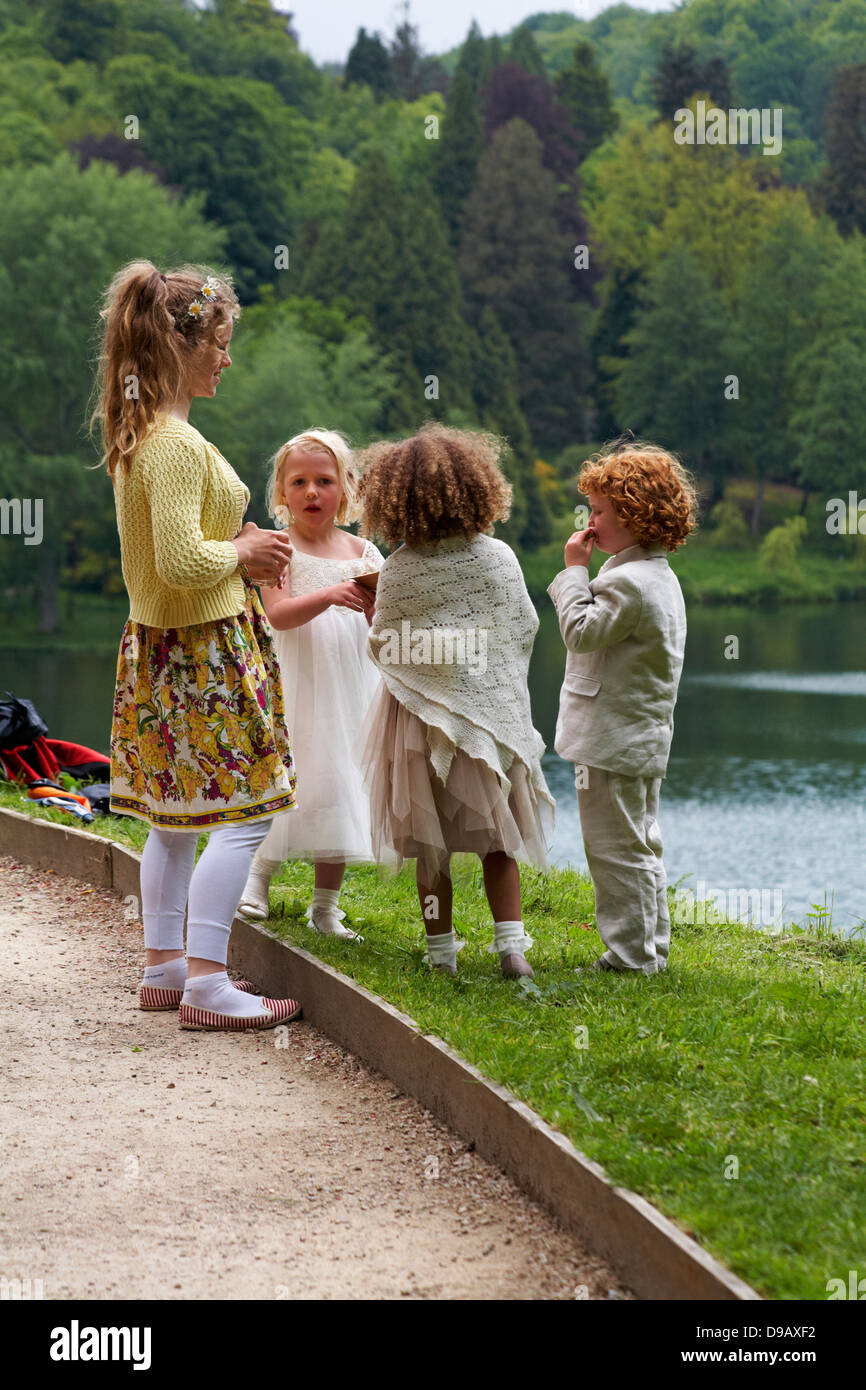 group of children eating strawberries at wedding ceremony in June - Stock Image