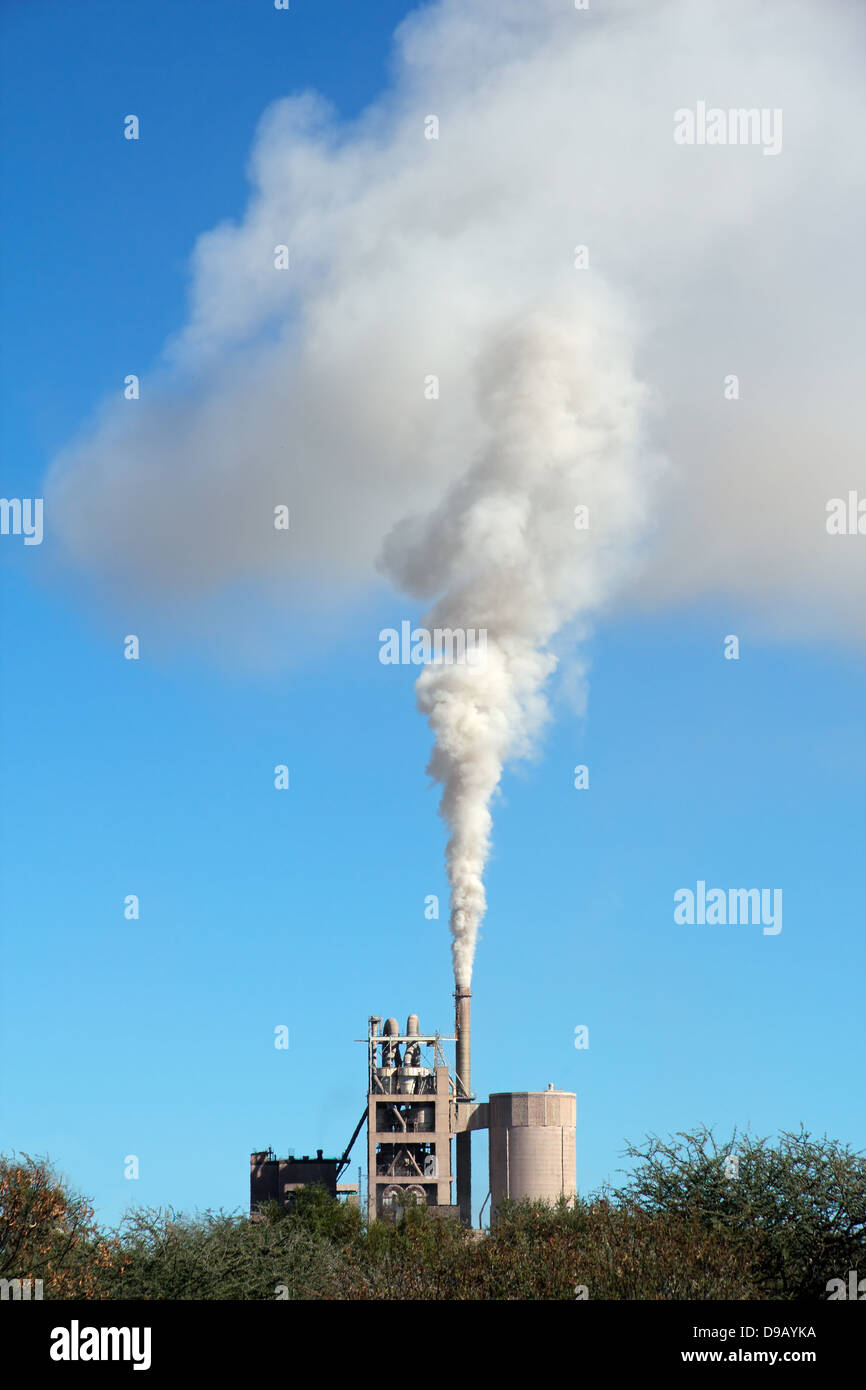 Smoke from an industrial plant drifting in the wind against a blue sky - Stock Image