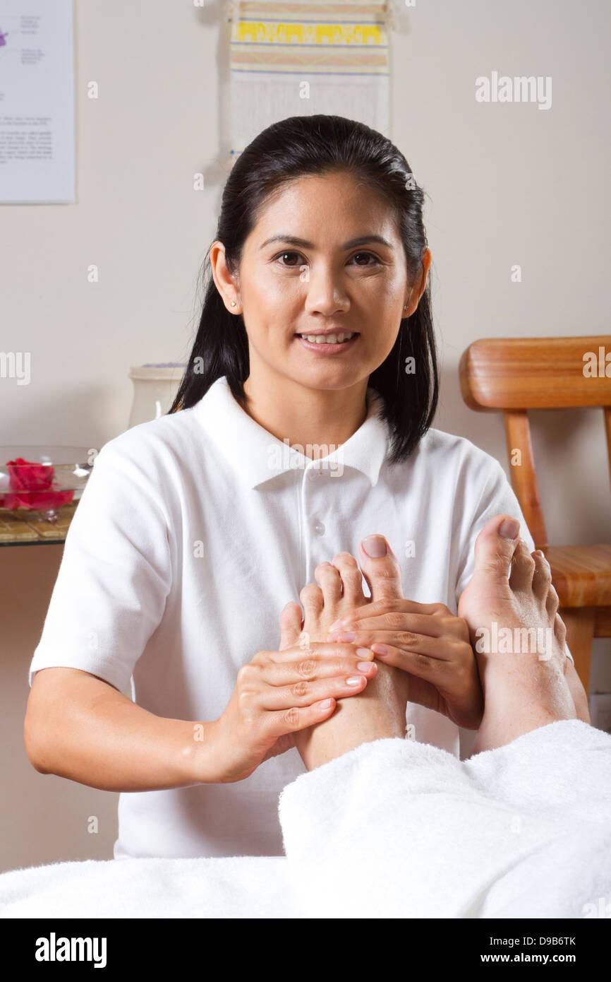 Asian masseuse giving professional foot massage Stock Photo