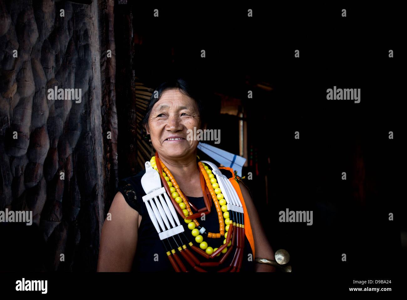 Naga tribeswoman in traditional outfit and smiling, Kisama, Kohima, Nagaland, India - Stock Image