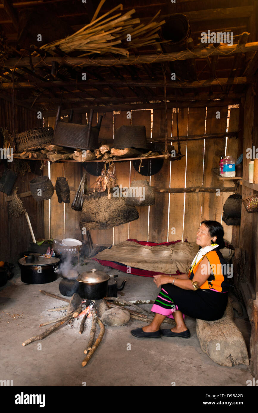 Naga tribeswoman cooking in a hut, Kisama, Kohima, Nagaland, India - Stock Image