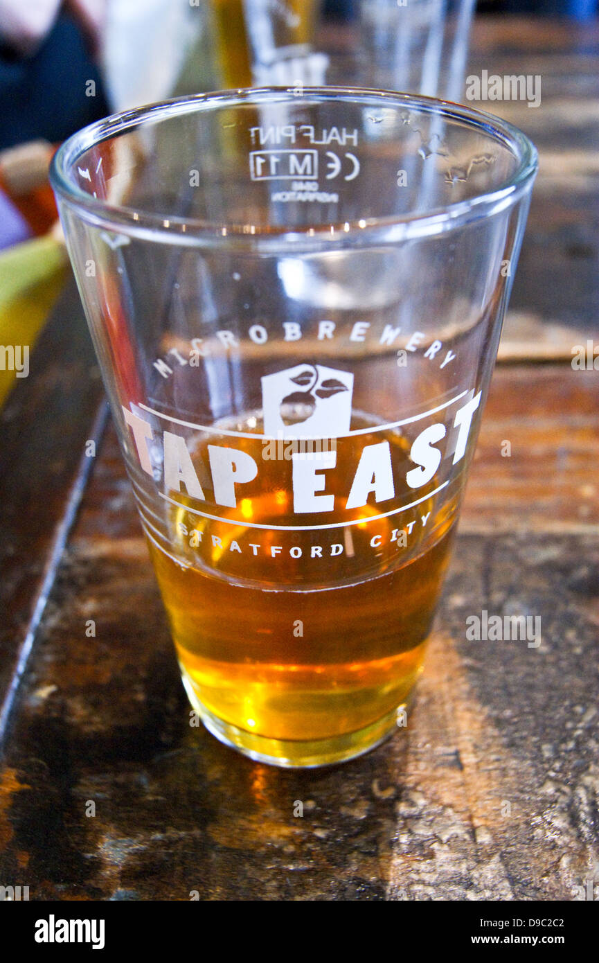 A pint of pale ale in a printed glass at Tap East bar, Westfield, Stratford, London, England. Cropped landscape Stock Photo