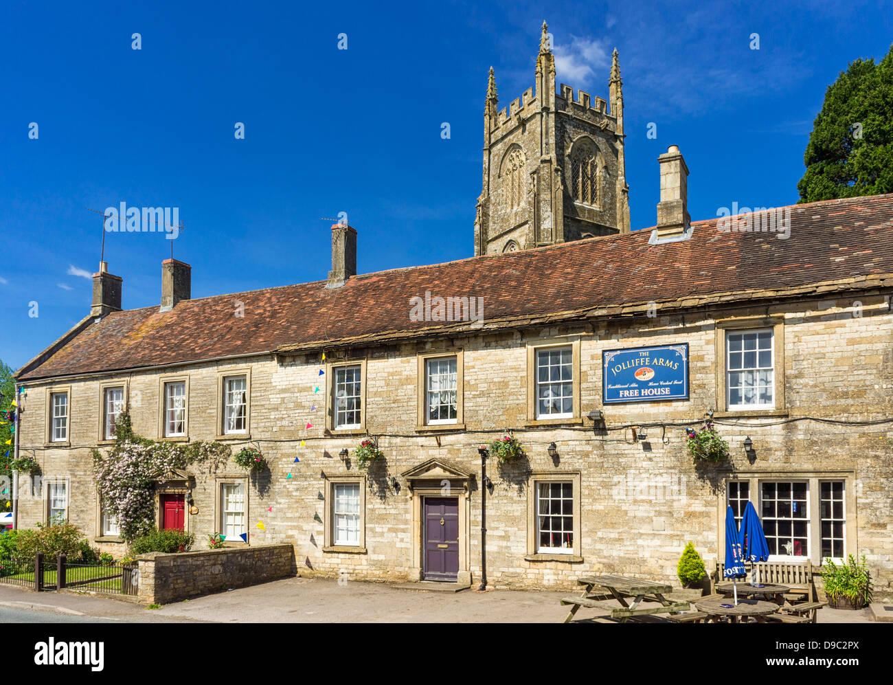 English village pub - Jolliffe Arms at Kilmersdon, Somerset, England, UK - with church behind - Stock Image