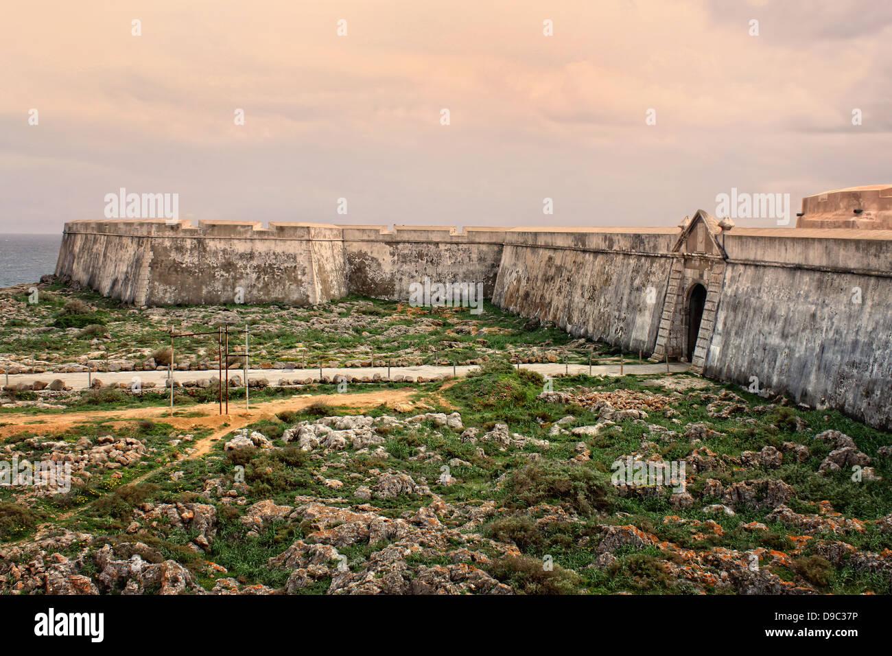 Rugged terrain surround the fortress in Ponta de Sagres, Algarve, Portugal - Stock Image
