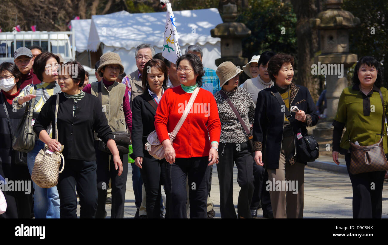 Japanese Tourists visiting Yasukuni Shrine during the Cherry Blossom Viewing Festival - Stock Image