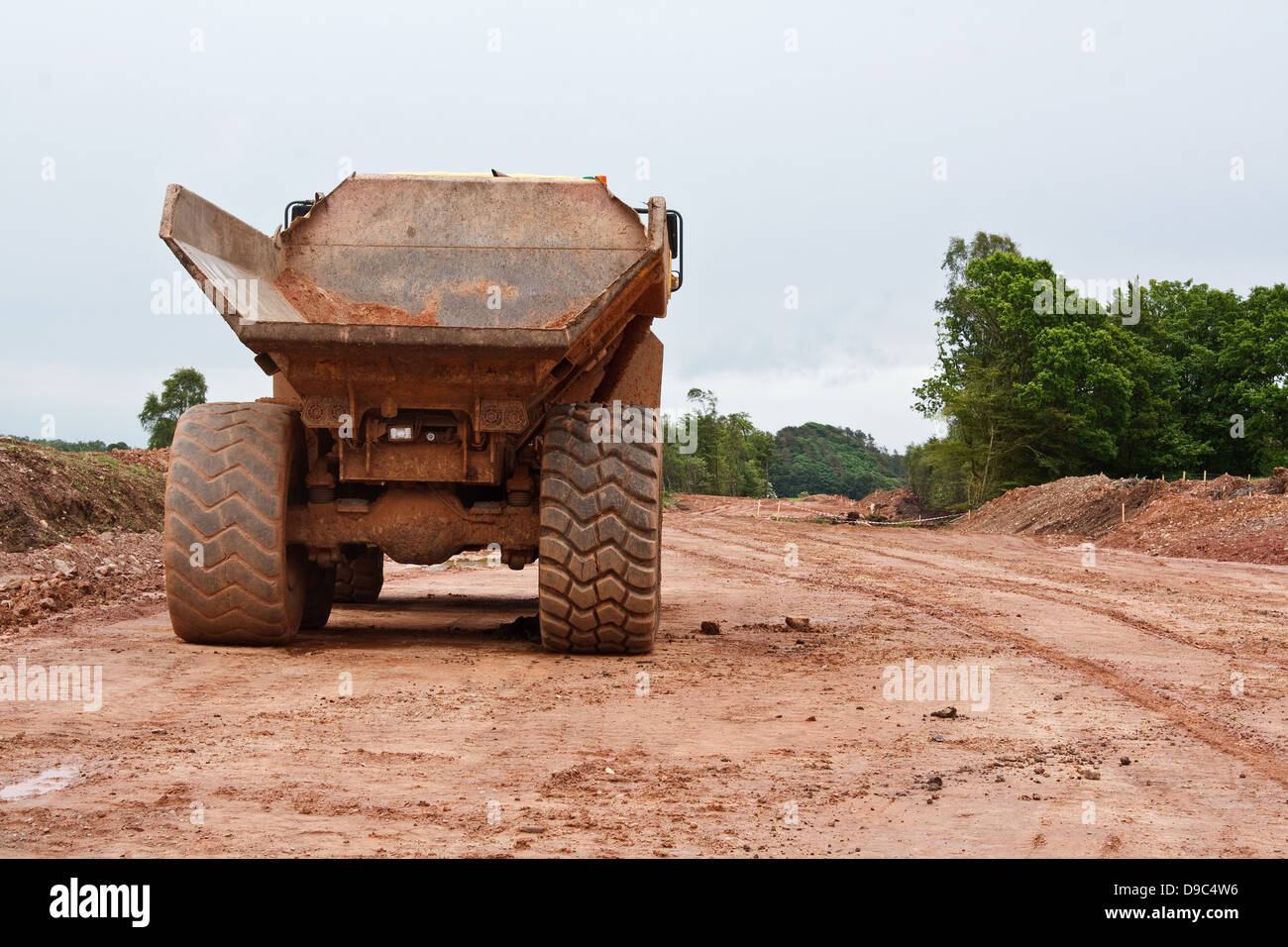 Heavy industrial dumper truck at a new road construction site - Stock Image