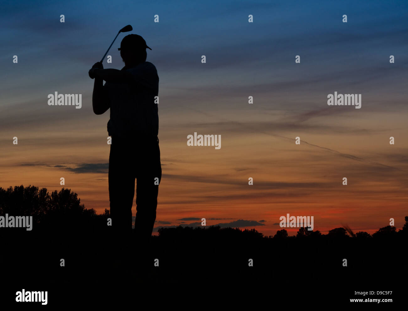 Silhouette of a Golfer teeing off early at dawn - Stock Image