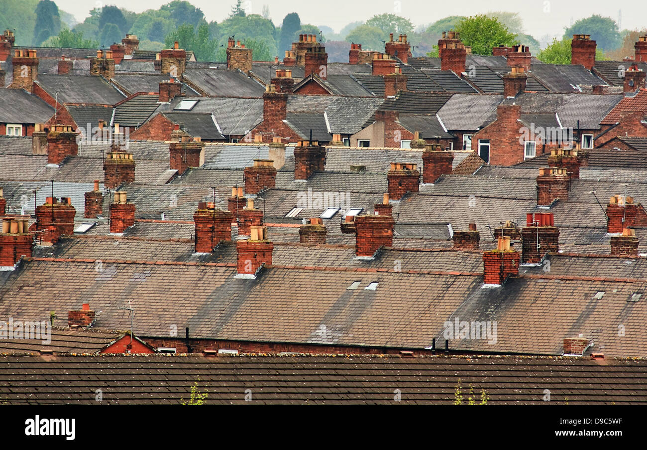 Urban scene across built up residential area of terraced houses showing the slate roof tops of an old housing estate - Stock Image