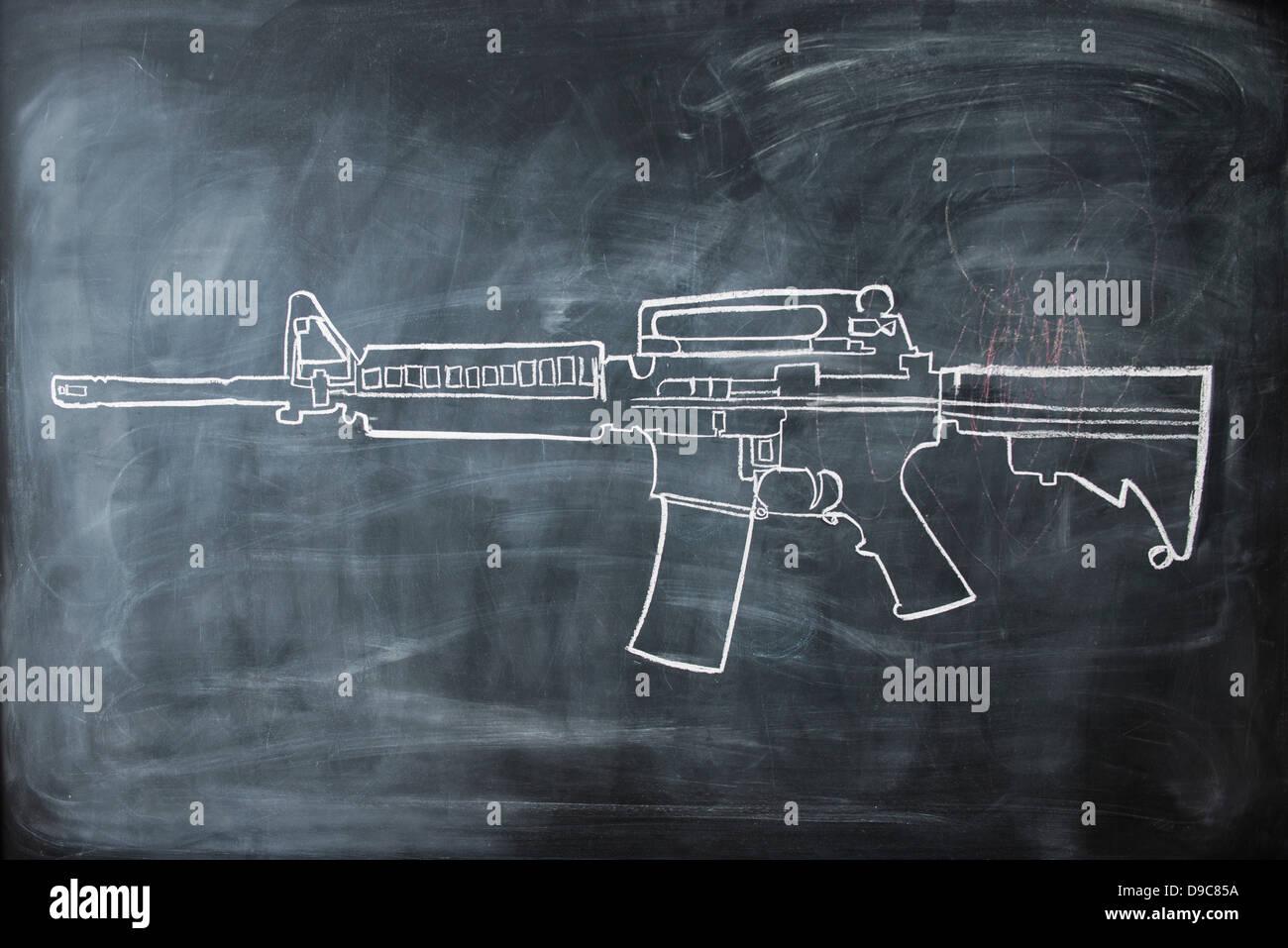 Chalk drawing of gun on blackboard Stock Photo