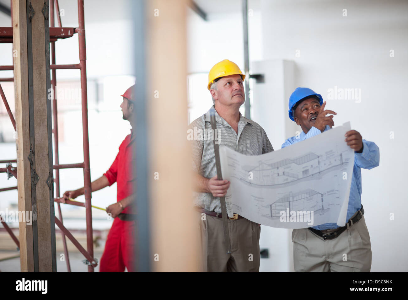 Construction workers taking break site stock photos construction construction workers pointing and looking with blueprint on construction site stock image malvernweather Choice Image