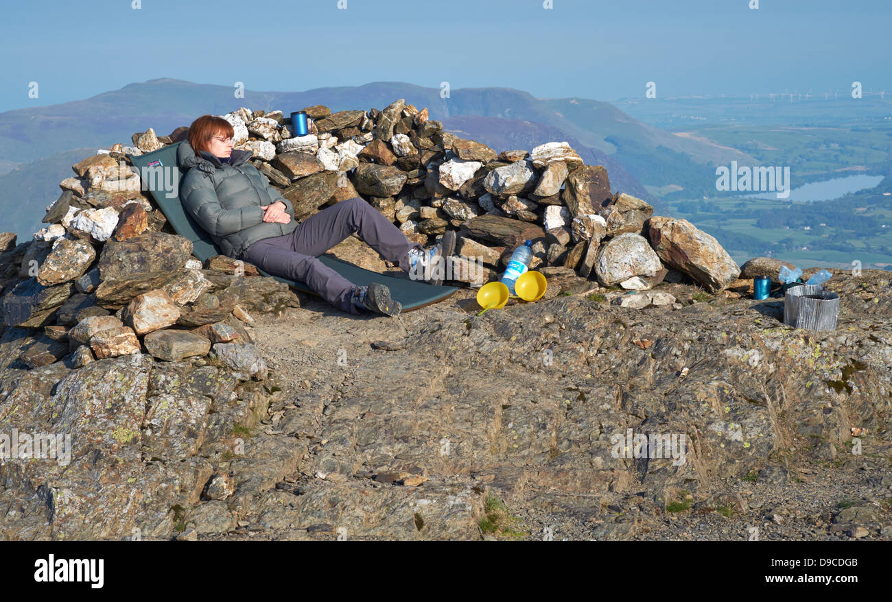 A hiker wild camping on the summit of Robinson in the Lake District - Stock Image