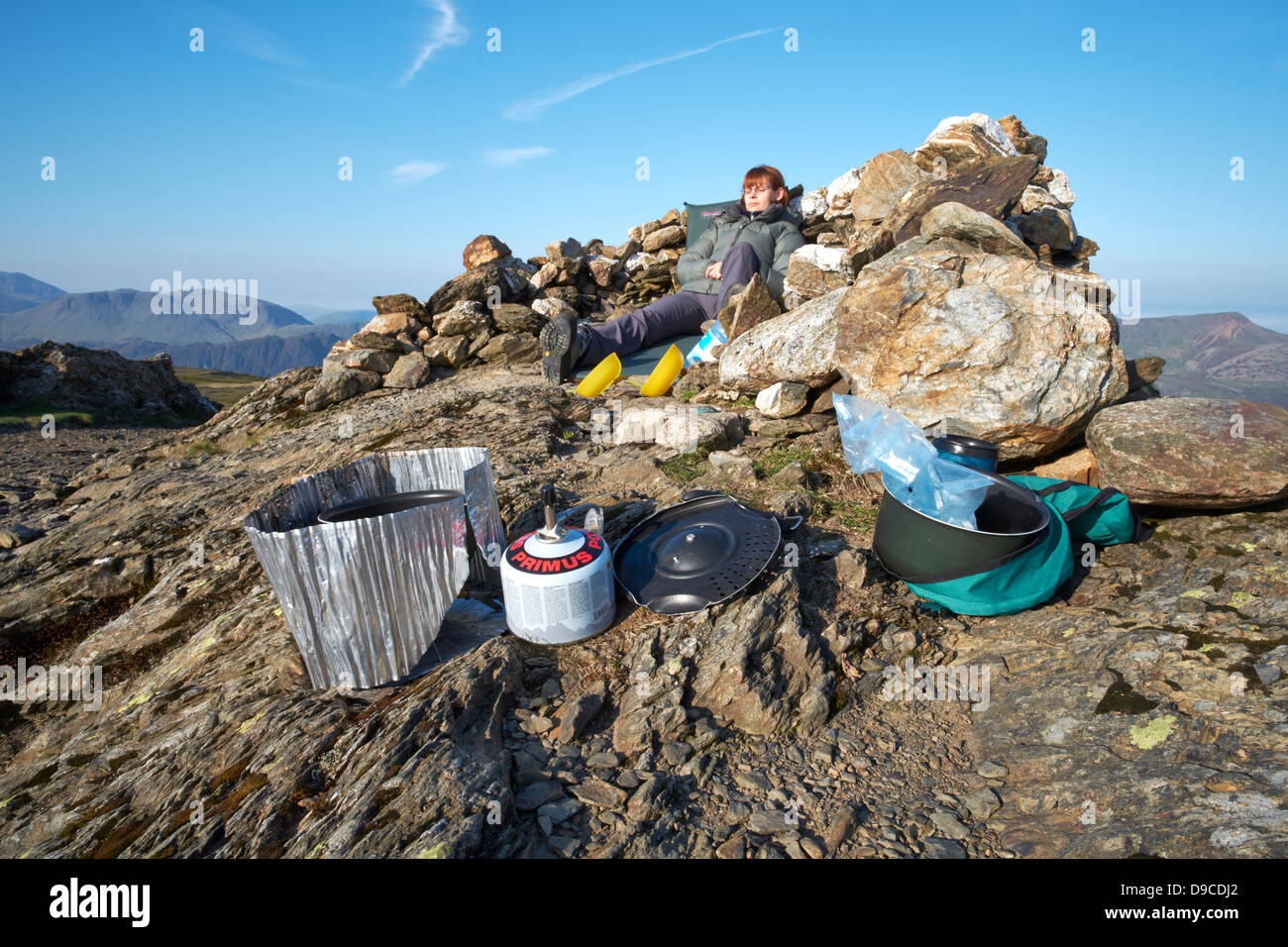 A hiker camping on the summit of a Robinson in the Lake District. - Stock Image
