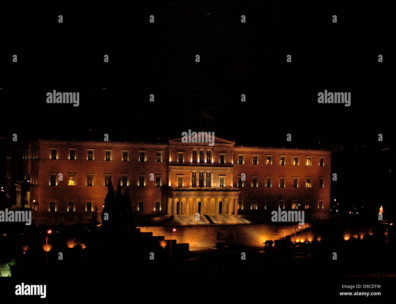 The Parliament Building (Old Palace) at night, Athens, Greece. An example of the early period of Neoclassicism in - Stock Image