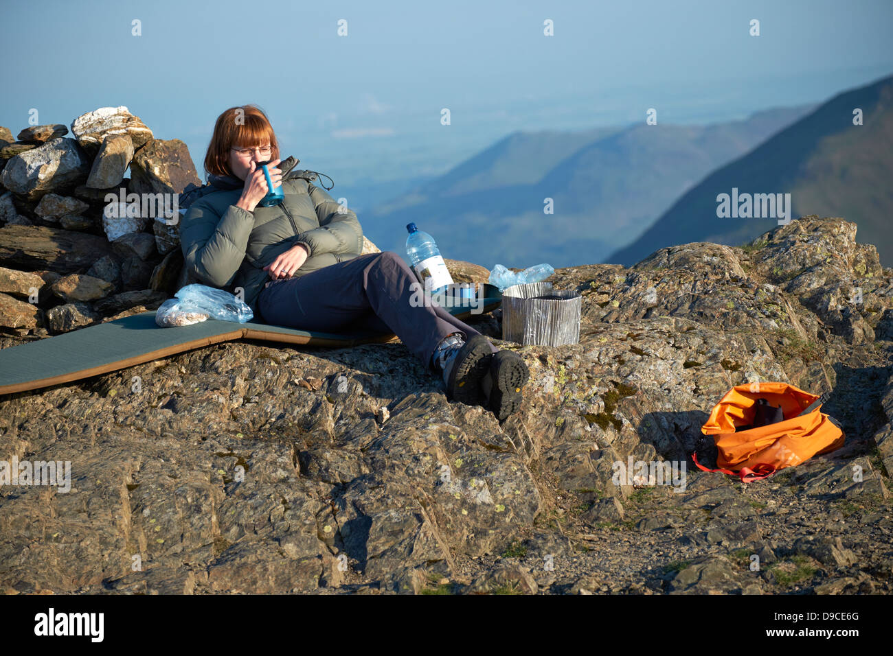 A female hiker enjoying an early morning cup of tea after camping on the summit of Robinson in the Lake District - Stock Image