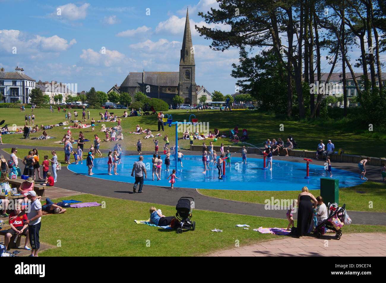 Families enjoying the summer at Silloth paddling pool on the green with Christ Church in the distance Cumbria England - Stock Image