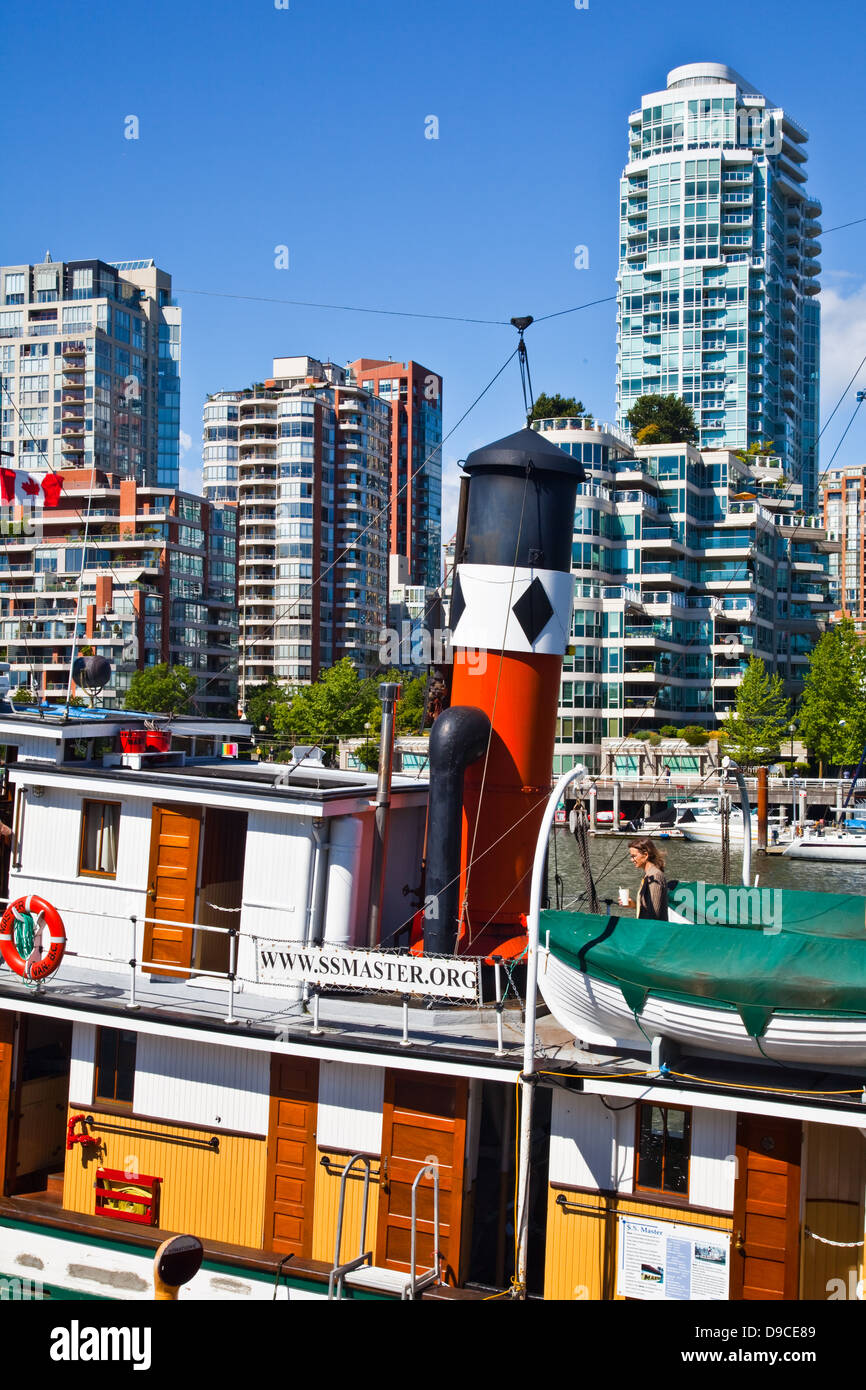 Brightly coloured vessel against the Vancouver skyline at Granville Island - Stock Image