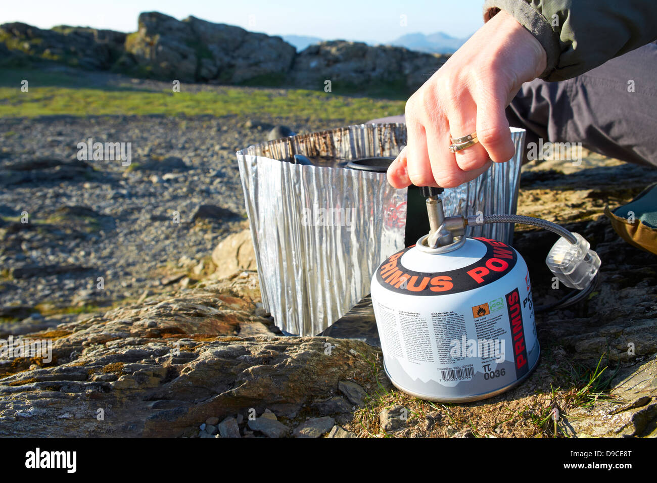 A hiker cooking on a camping stove on the summit of a Robinson in the Lake District. - Stock Image