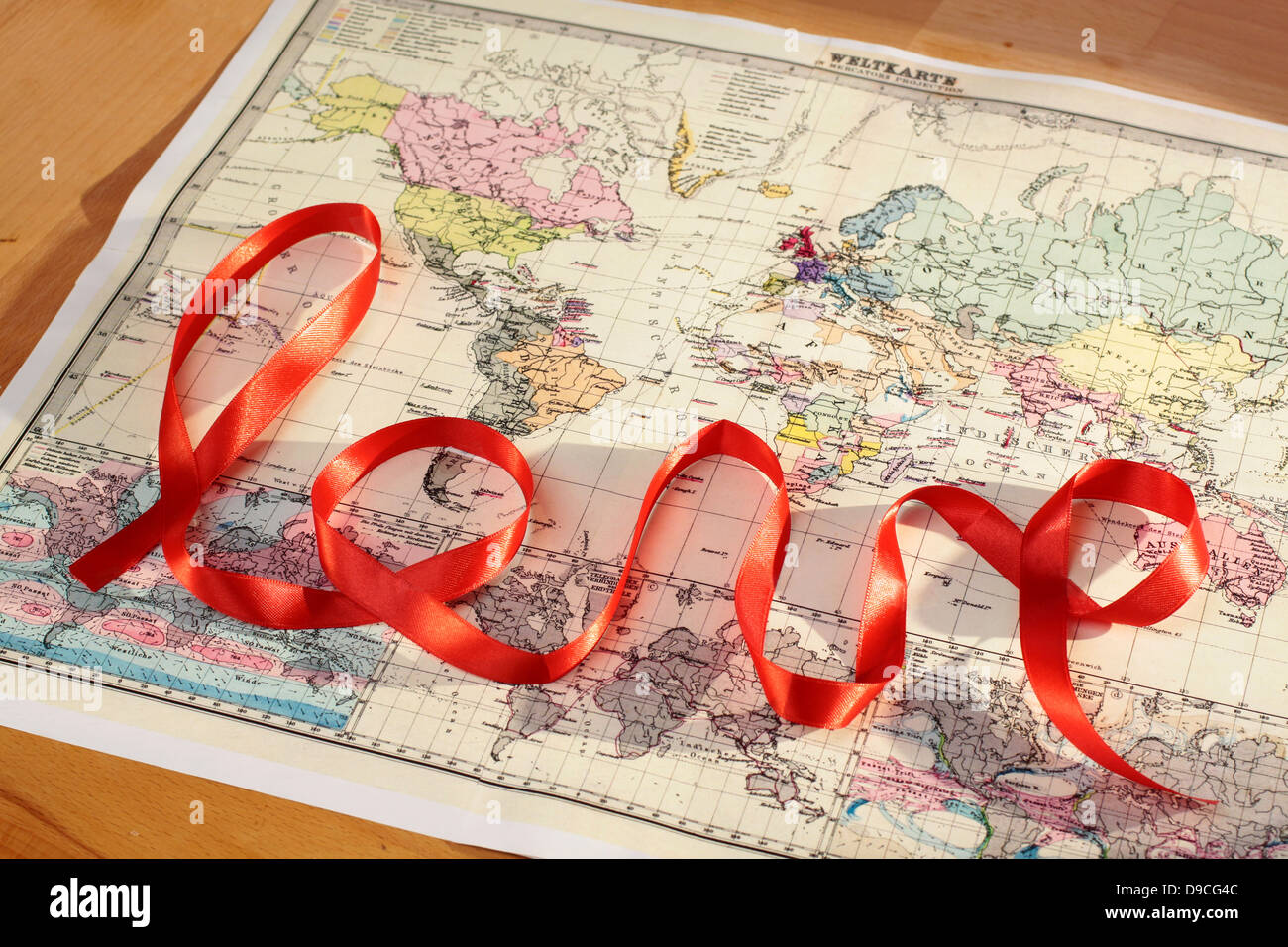 Red lettering love over historic world map - Stock Image